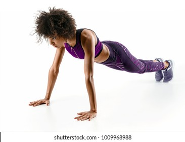 Strong girl doing push up. Photo of sporty african girl doing exercising isolated on white background. Strength and motivation