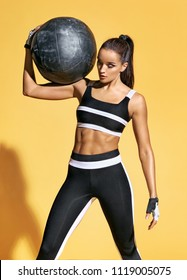 Strong girl holding med ball on her shoulder. Photo of sporty latin woman in fashionable sportswear on yellow background. Strength and motivation.