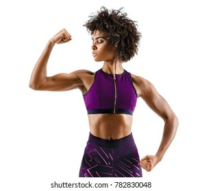Strong girl with perfect abs, shoulders, biceps, triceps and chest. Photo of sporty young african girl on white background. Strength and motivation