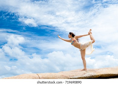 A strong girl Wearing a swimsuit And pretend to practice yoga On the beach by the sea There is a background of sea and bright sky.