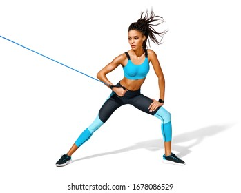 Strong girl working with resistance band. Photo of african american girl in fashionable sportswear on white background. Dynamic movement. Full length. Sports and healthy lifestyle