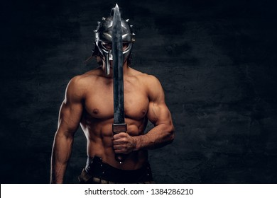 Strong gladiator with sword in his hands. He is wearing gladiator's bandage and helmet.