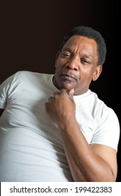 Strong good looking mature African American working man against a dark background