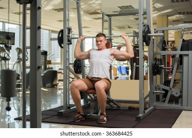 Strong guy with barbell. Sportsman concentrated on the sport. Young man is pushing barbell.