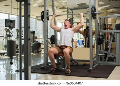 Strong guy with barbell. Young man is pushing barbell. Sportsman concentrated on the sport.