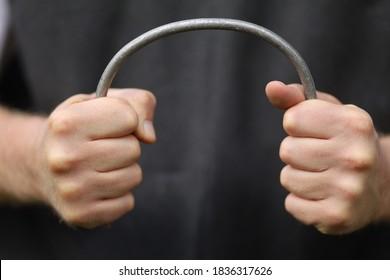 Strong hands bend a metal rod