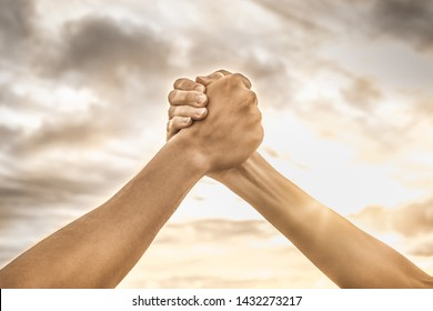 Strong hands coming together grasping one another, helping hand. People working together, unity, teamwork