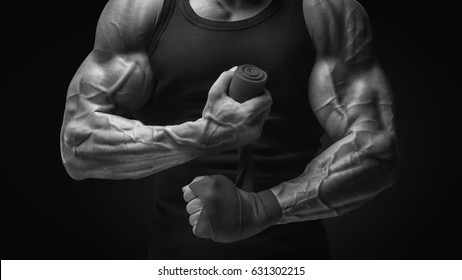 Strong hands and fist, ready for training and active exercise Close-up photo of strong man wrap hands Man is wrapping hands with boxing wraps isolated on black background