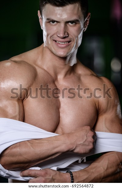 Strong and handsome athletic young man with muscles abs and biceps. Close-up of a power fitness man on diet