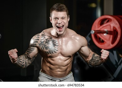 Strong and handsome athletic young tattoo man with muscles . Close-up of a power fitness man on diet abs and biceps