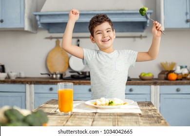 I am strong. Handsome cheerful dark-haired little boy having healthy breakfast and smiling and showing his muscles
