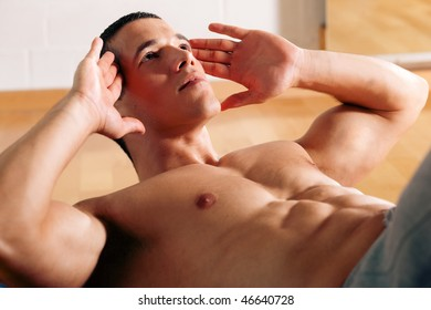 Strong, handsome man doing sit-ups in a gym as bodybuilding exercise, training his muscles