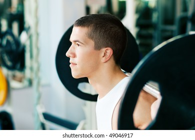 Strong and handsome man lifting weights - a barbell - in a gym