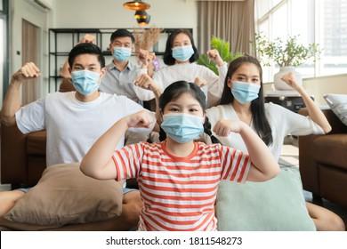 starke gesunde asiatische Familie, die eine chirurgische Schutzmaske tragen, bleiben in der Familie zu Hause Quarantäne, die neue normale Lebensweise