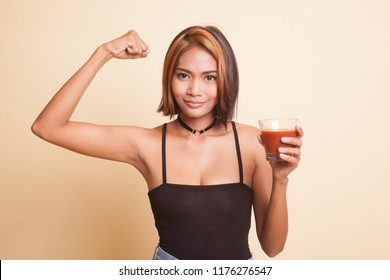 Strong healthy Asian woman with tomato juice on beige background