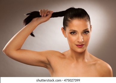 strong healthy hair - Woman holds a pony tail over gray background