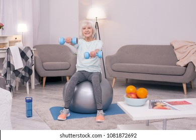 Strong and healthy. Joyful elderly woman sitting on a yoga ball and holding a pair of dumbbells while carrying out strengthening exercises
