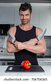 Strong healthy muscle sporty looking handsome charismatic smiling man bodybuilder in black tank top with knifes in hands and red bulgarian pepper on cutting board in white high tech style kitchen