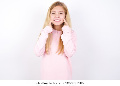 Strong healthy straight white teeth. Close up portrait of happy beautiful caucasian little girl wearing pink sweater over white background with beaming smile pointing on perfect clear white teeth.