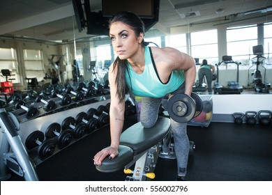 Strong, healthy woman lifting weights in the gym during a workout