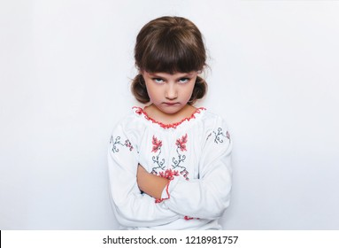 Strong independent Ukraine opposes the enemy. A small offended girl stands with arms crossed. Children's protest. White background. Copy space.