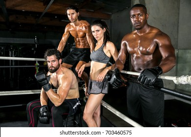 Strong intense intimidating muscular athletes posing together in a group at a boxing gym