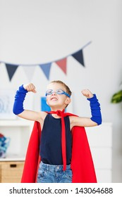 Strong kid wearing a superhero costume and showing his muscle