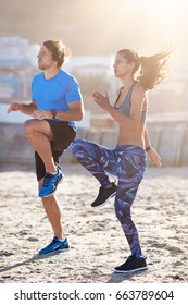 Strong lean couple doing intense high knees exercise on sand, keeping fit healthy lifestyle
