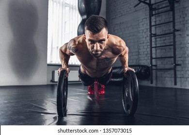 Strong like a stone. The athlete trains in the gym, doing strength exercises for muscles, push-up or press up, work on his body with weights and barbells. Fitness, healthy and self-control concept.