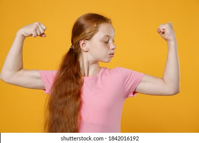 Strong little ginger redhead kid girl 12-13 years old wearing pink casual t-shirt posing showing biceps muscles looking aside isolated on bright yellow color wall background children studio portrait