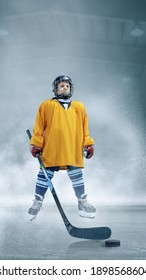 Strong. Little hockey player with the stick on ice court and smoke background. Sportsboy wearing equipment and helmet training in action. Concept of sport, childhood, motion, movement, action.