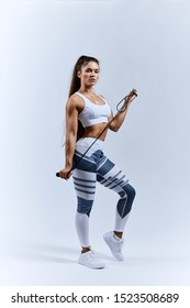 strong lovely sportswoman holding skipping rope and posing to the camera, full length photo. isolated white background