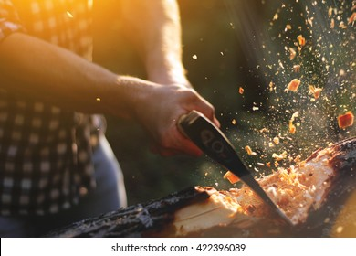 Strong lumberjack chopping wood, chips fly apart