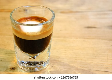 Strong macchiato coffee in small glass on wooden table. Reflections.  Stay focused concept.
