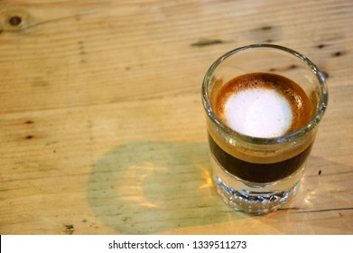 Strong macchiato coffee in small glass on wooden table. Reflection, shadow.  Stay focused concept.