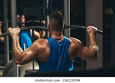 Strong male bodybuilder doing exercise for back with lat pulldown machine in gym