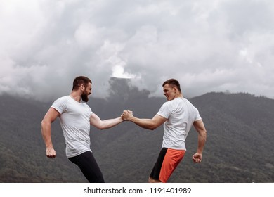 Strong male bodybuilders in white t-shirts greeting each other in arm wrestling manner, outdoor over foggy mountain landscape. Rivalry, challenge, strength comparison concept