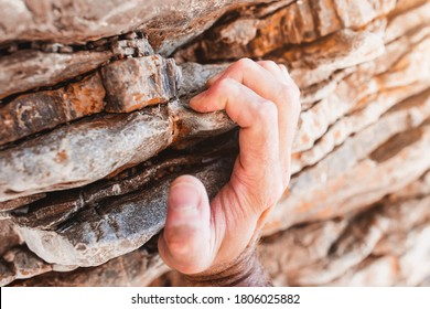 Strong male fingers cling to a rock ledge - close-up rock climbing
