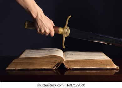 Strong male hand with sword on top of open Bible
