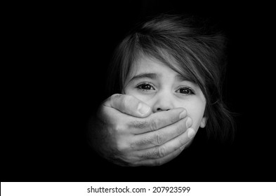 Strong male hands cover young girl face with emotional stress, pain, afraid, call for help, struggle, terrified expression.Concept photo of abduction, missing, kidnapped,victim, hostage,child abusing