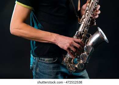 Strong male hands hold the silver saxophone while pushing on the buttons to produce the beautiful melody. Casual style of the busker: black T-shirt with jeans.