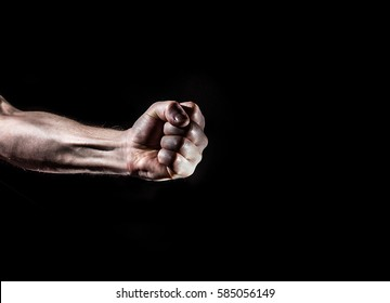 strong male man raised fist on a black background, power, protest, fist ready to fight