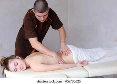 Strong male physician conducts easy and relaxing massage, relieves fatigue and tension with help of medical procedure and quiet movements of hands leads along back of girl's client who came to