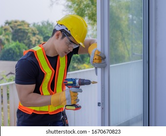 Strong male workers penetrate the wall, work hard for men. Strong worker, repair, piercing the wall, the man in the helmet, the concept of repair and renovation of buildings.