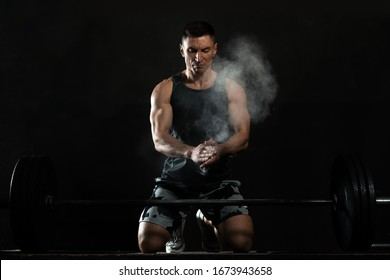 Strong man applying magnesium powder on hands before training with barbell in gym