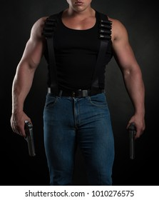 Strong man bodybuilder with pistols