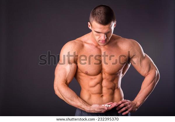 Un homme fort, culturiste, posant sur fond gris. Un homme tenant une pilule, des acides aminés, des compléments alimentaires. Il les regarde. Sports, musculation, nutrition sportive spéciale.