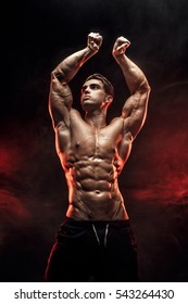 Strong Man Bodybuilder with Six Pack and perfect abs, shoulders, biceps, triceps and chest, personal fitness trainer flexing his muscles in red smoke.