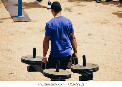 Strong man carrying heavy barbells in competition
