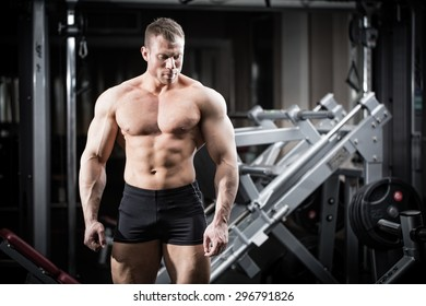 Strong man doing bodybuilding in gym standing in front of a dumbbell rack